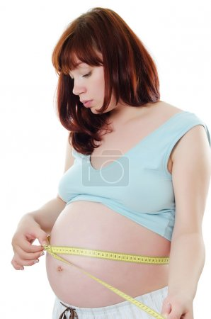 Pregnant woman with a measuring tape