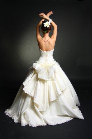 Photo pour Mannequin portant la robe de mariée à fond de studio noir - image libre de droit