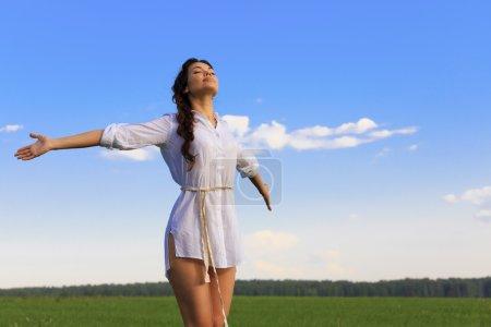 Photo pour Jeune femme heureuse dans un champ vert, lumière du soir - image libre de droit