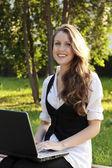 Hezká mladá žena s laptopem sedí na lavičce v parku