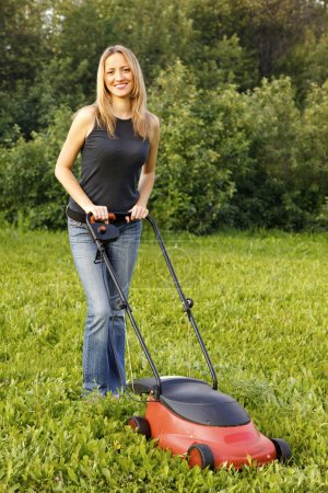 Photo pour Femme tondre avec une tondeuse à gazon - image libre de droit