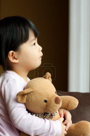 Photo pour Triste petite fille détient qu'un ours en peluche se penche sur la fenêtre. le ressentiment et l'attente - image libre de droit