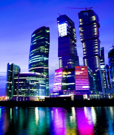 Night city of business skyscrapers in vibrant colors