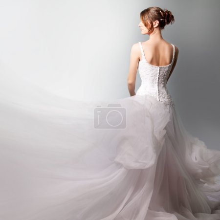 Photo for The beautiful high bride in a luxurious wedding dress, on a white background - Royalty Free Image