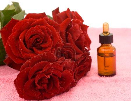 Photo pour Bouquet de roses rouges et huile de rose sur la serviette rose - image libre de droit