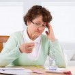 Постер, плакат: Elderly woman worry about bill notice