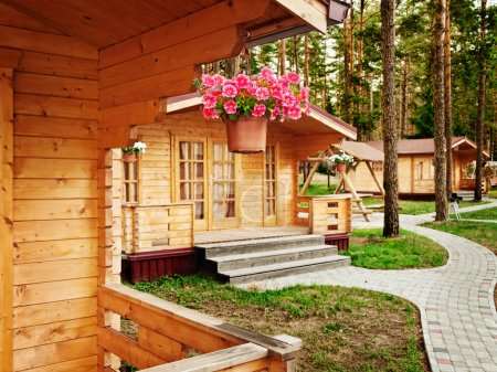 Photo for Houses with flowers in the pine forest - Royalty Free Image