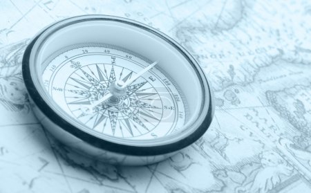 Photo for Old compass on ancient map. Blue toned image - Royalty Free Image