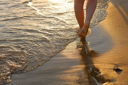 Photo for Footprint on sand. Sunset illumination, a fragment of female feet - Royalty Free Image