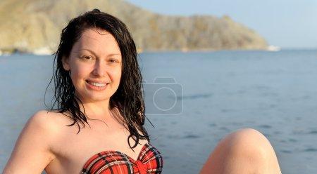 The joyful woman sits on sea coast
