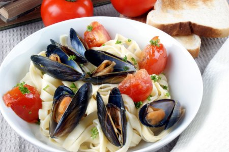 Pasta with mussels and grilled tomatoes on a plate