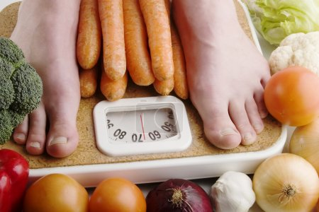 Photo for A pair of female feet standing on a bathroom scale with vegetables pilled around. - Royalty Free Image