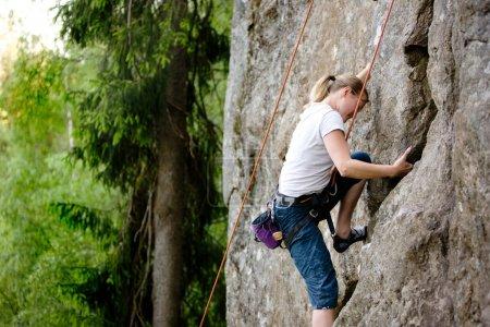 Foto de Una escaladora, trepando con una cuerda superior sobre una empinada roca (peñasco) ) - Imagen libre de derechos
