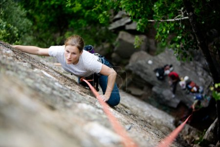 Photo for A female climber on a steep rock face. Shallow depth of field is used to isolated the climber. Focus is on the head, shoulders and arms of the climber. - Royalty Free Image