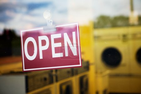 Photo for An open sign hanging in a window of a laundromat - Royalty Free Image