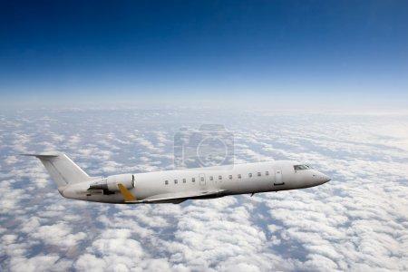 Photo pour Avion en vol au-dessus de nuages de haute altitude - image libre de droit