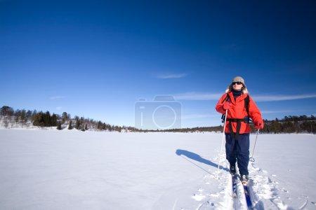 A woman cross country skiing across a frozen lake...