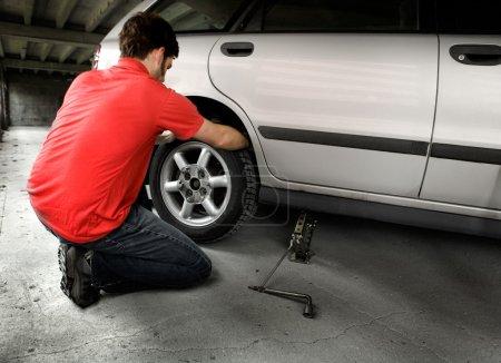 Photo pour Un homme caressant un pneu sur une voiture dans un garage - image libre de droit