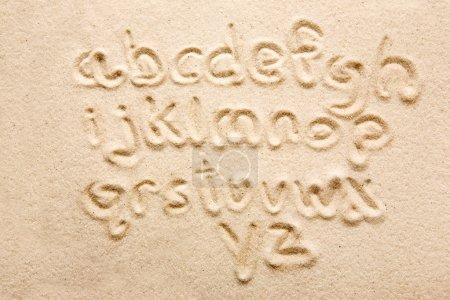 Photo pour Alphabet minuscule écrit dans le sable - un outil de concepteurs - image libre de droit