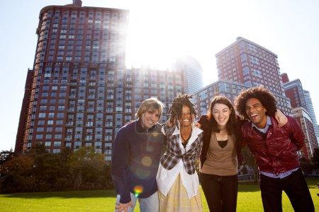 Photo pour Un groupe de jeunes adultes dans un parc de la ville - tourné vers le soleil avec éruption solaire - image libre de droit