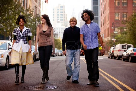 Photo for A group of young walking down a street in a large city - Royalty Free Image