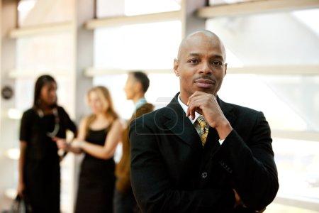 Photo pour Un homme d'affaires américain avec ses collègues en arrière-plan - image libre de droit