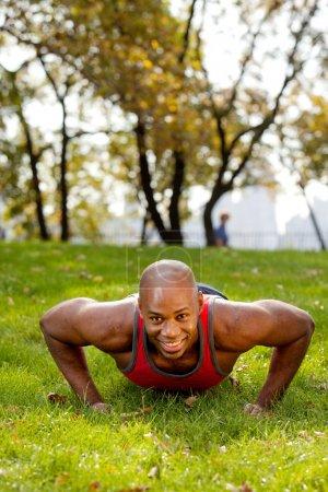 Foto de Un afroamericano haciendo push ups en el parque - Imagen libre de derechos