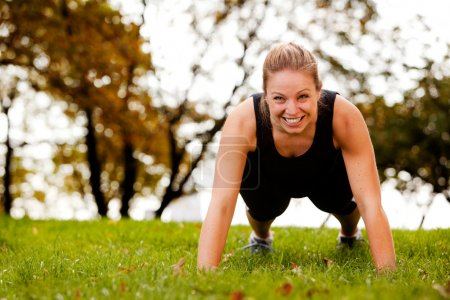 Photo for A woman doing push-ups in the park - Royalty Free Image