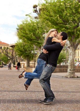 Photo pour Un couple européen heureux l'homme soulevant et embrassant la femme - image libre de droit