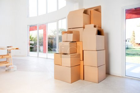 Photo for A stack of moving boxes in a new house, ready to unpack - Royalty Free Image