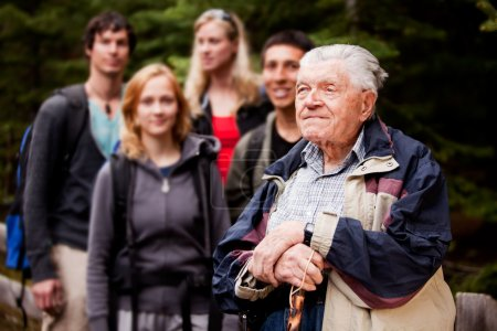 Photo for An elderly man giving a tour for a young group of - Royalty Free Image