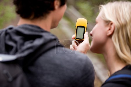 A couple outdoors in the forest using a GPS