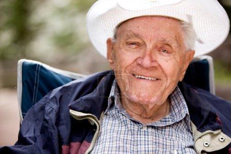 Photo pour Portrait d'un vieillard souriant et heureux assis à l'extérieur - image libre de droit
