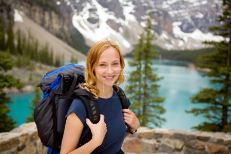 Photo for A portrait of a young happy woman infront of a beautiful mountain landscape - Royalty Free Image