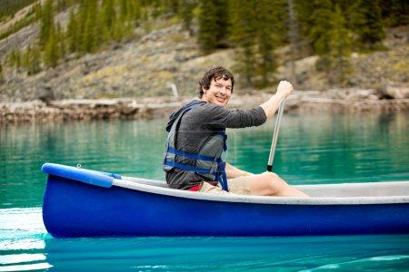 Photo pour Portrait d'un homme souriant dans un canot sur un lac glaciaire - image libre de droit