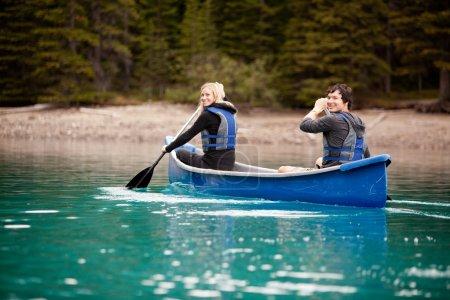 Photo pour Un homme et une femme pagayant dans un canot sur un lac - image libre de droit