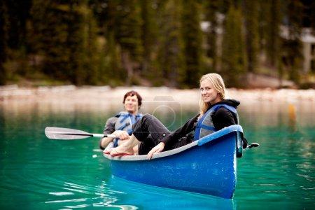 Photo pour Un couple heureux et relaxant dans un canot sur un lac glaciaire - image libre de droit