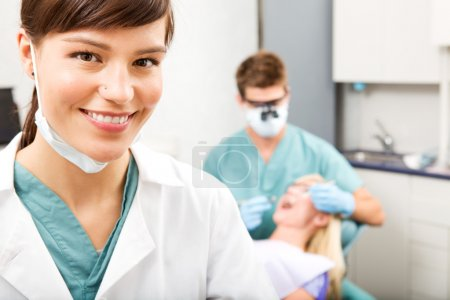 Photo for A portrait of a dental assistant smiling at the camera with the dentist working in the background - Royalty Free Image