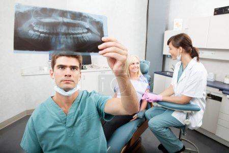 Photo pour Radiodentiste vérifiant la radiographie avec assistant et patient ayant une conversation en arrière-plan - image libre de droit