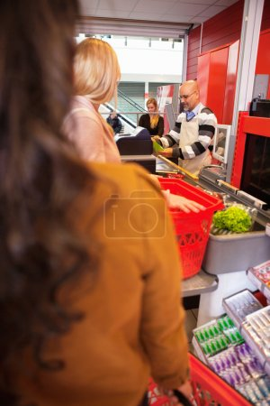 Shop assistant with customers
