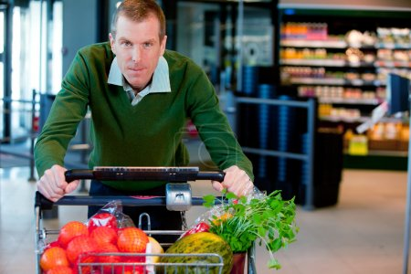 Photo for Portrait of a man pushing a grocery cart in a supermarket - Royalty Free Image