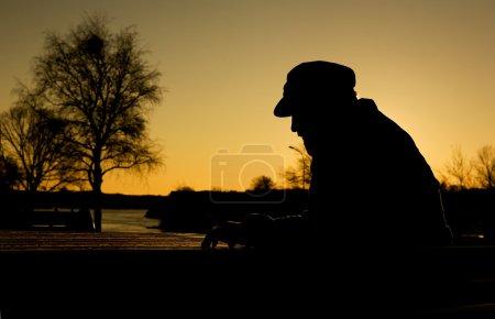 Photo pour Un homme attentionné déprimé par l'eau au coucher du soleil. lumière du soleil chaleureux créant une silhouette. - image libre de droit