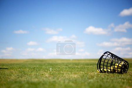 Photo pour Un tee et des balles de golf jaunes sur un practice - image libre de droit