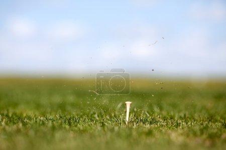 Photo pour Les effets secondaires d'une oscillation de golf. Faible profondeur de champ en mettant l'accent sur le tee - image libre de droit