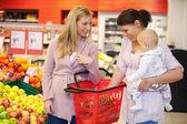 Mutter mit Kind mit Freund beim Einkaufen