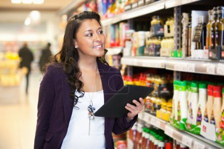 Foto de Mujer sonriente mirando los productos mientras sostiene la tableta digital con en el fondo - Imagen libre de derechos