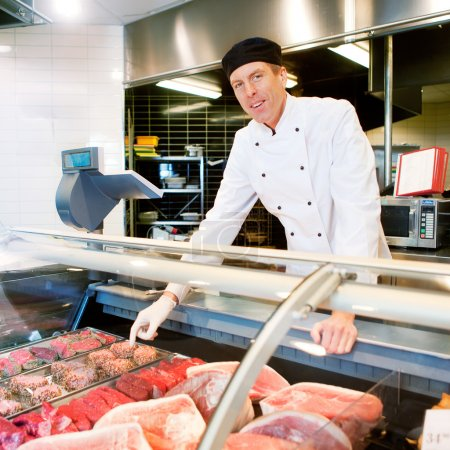 Photo for A butcher at a fresh meat counter or deli in a store - Royalty Free Image
