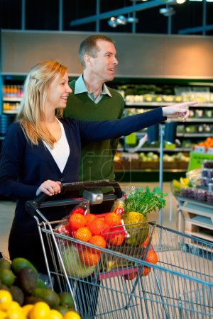 Photo for A happy couple in a supermarket buying groceries - Royalty Free Image