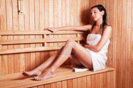 Photo pour Belle jeune femme se détendre dans un sauna finlandais - image libre de droit