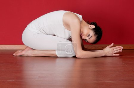 Young woman in a exercise clothing in a yoga pose